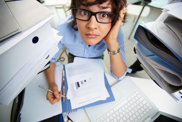 perplexed accountant doing financial reports surrounded by huge piles of documents