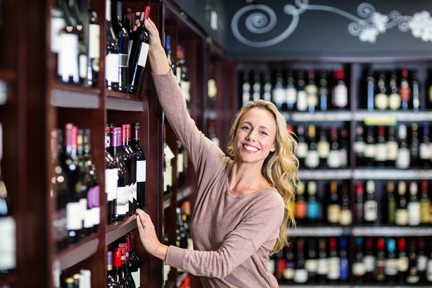 smiling woman picking bottle of wine