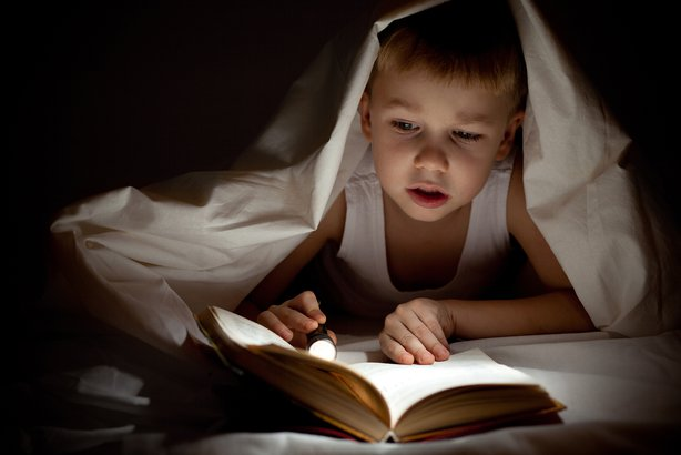 boy reading book in bed