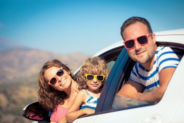 father, mother, and child hanging out of car windows