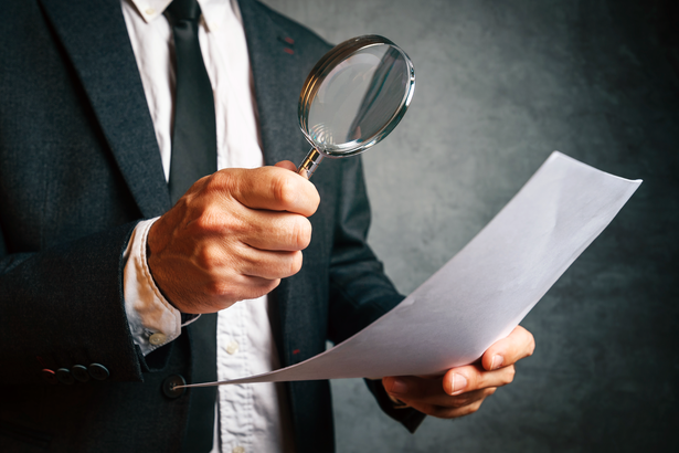 IRS employee investigating tax document with a magnifying glass