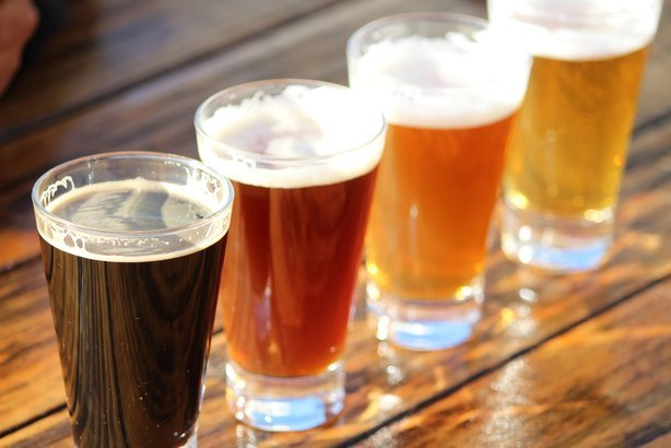 selection of four craft beers during a tasting session on a wooden table