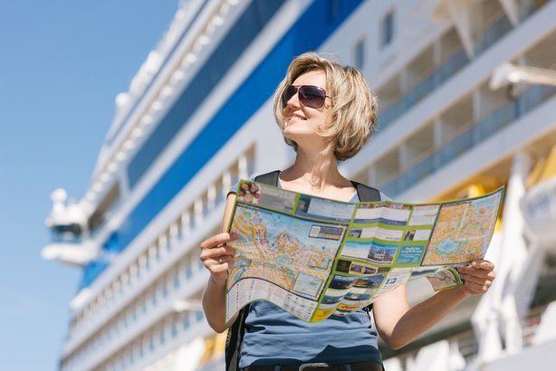woman tourist on shore with a map, standing in front of big cruise liner