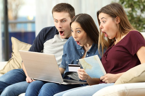 three amazed friends finding trip offers on line with a laptop sitting on a couch