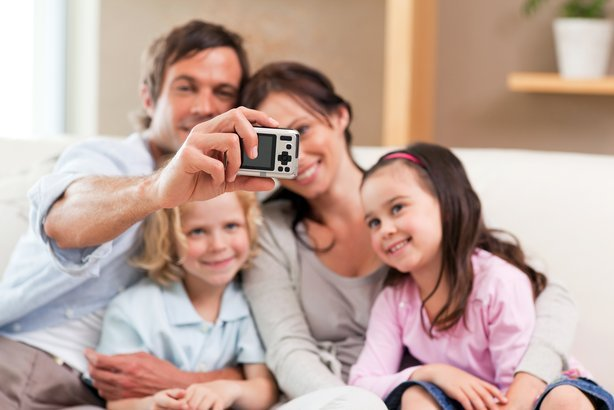 happy father taking a picture of his family in a living room