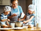 happy family in the kitchen. mother and children preparing the dough for baking
