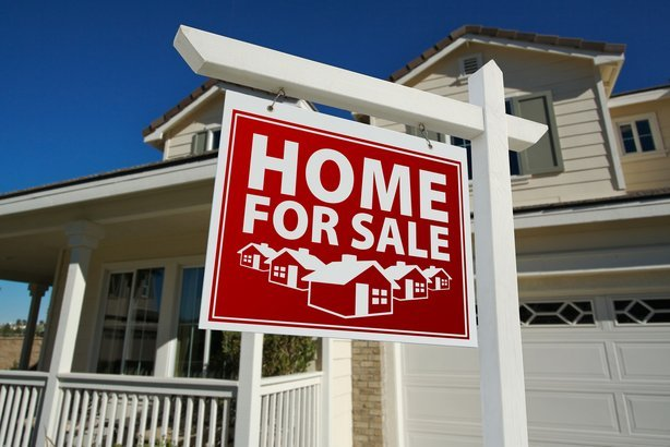 red 'Home For Sale' sign with house in the background