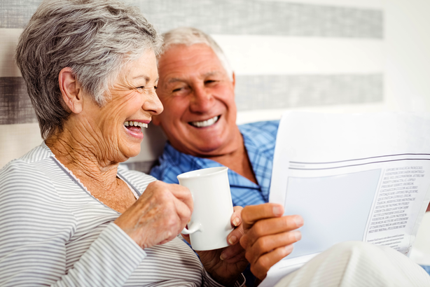 Senior couple enjoying coffee and reading the newspaper in bed