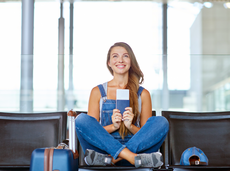 Excited young woman sitting in an airport with her ticket