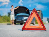 red warning triangle on road with broken car and person on cell in background