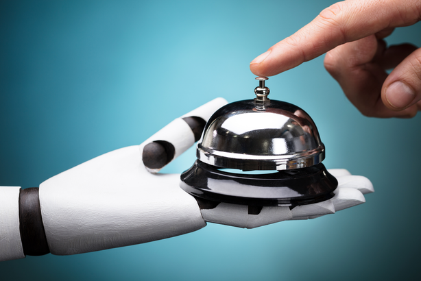 Robot hand holding out a bell for a person to ring