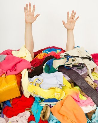 hands reaching out from a big pile of clothes and accessories