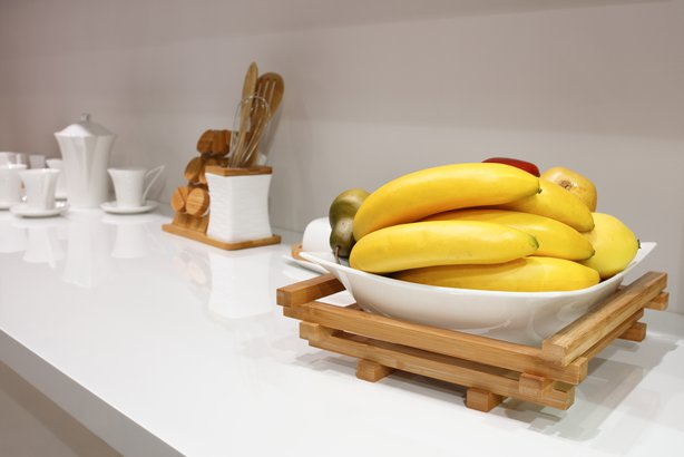 white kitchen with bananas and fruit on the table