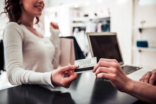 Woman shopping in a retail store and paying with a credit card