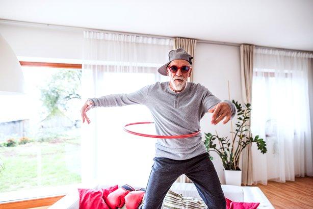 senior man doing hula hoop in living room