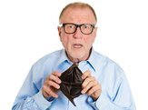 shocked senior man holding empty wallet