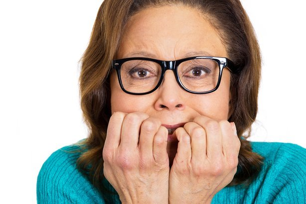 senior nerdy woman wearing glasses biting fingernails in stress