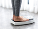 Woman's feet standing on a scale