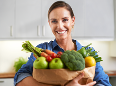 Woman holding grocery bag full of produce