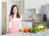 Happy woman in her kitchen holding a glass of water next to an assortment of healthy food