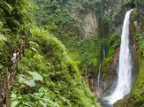 woman standing in front of towering tropical waterfall in Costa Rica