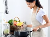 woman standing by the stove in the kitchen, cooking