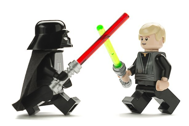 Lego Star Wars minifigure Darth Vader and Luke Skywalker are fighting with swords