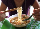 woman eating noodles in Vietnam at restaurant