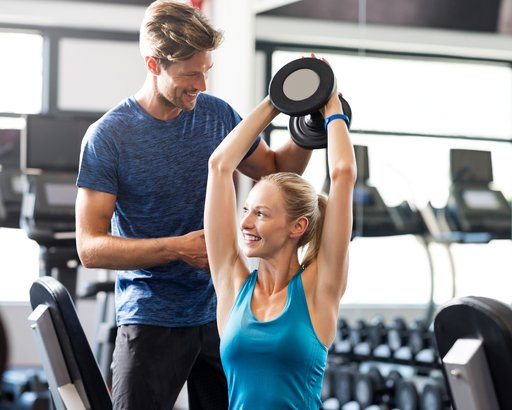 woman lifting weight with personal trainer