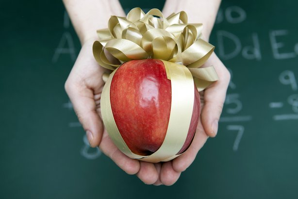 gifted apple in hands of student against blackboard