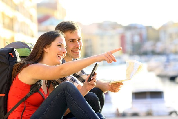 two happy tourists searching location together with a phone and map and pointing with the finger