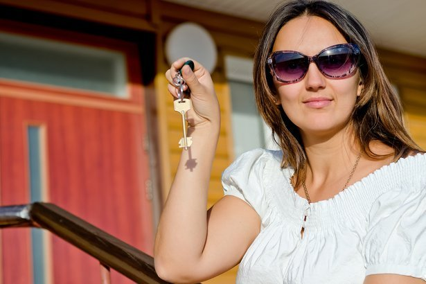 woman wearing sunglasses holding a house door key in her hand