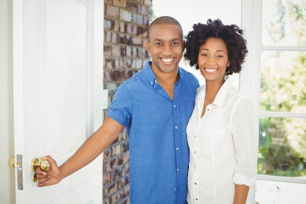 happy African American couple about to open the door of their house