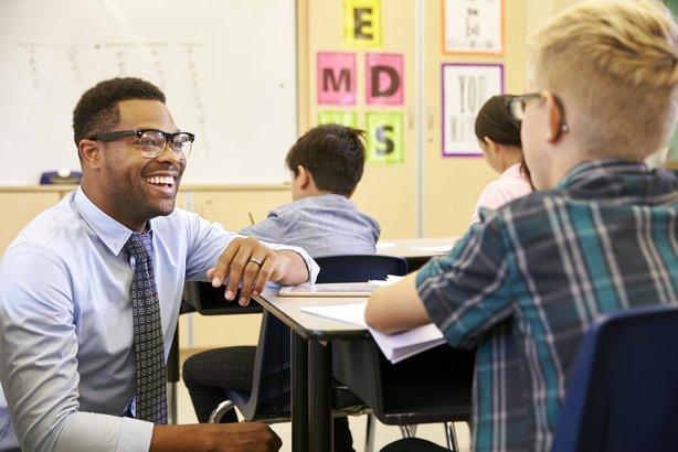 smiling teacher kneeling beside elementary student desk