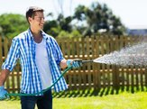 cheerful man watering home garden