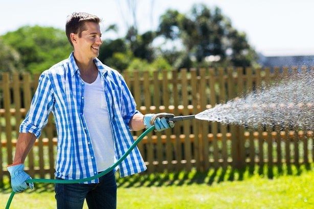 cheerful man watering home garden