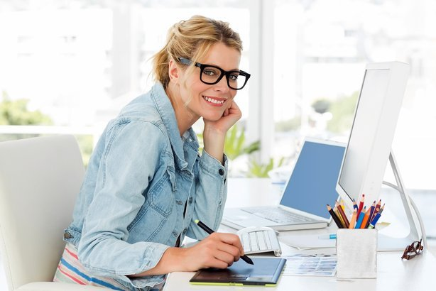 female designer looking at the camera using digitizer in creative office