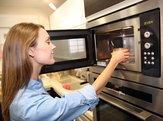 woman heating dish in microwave
