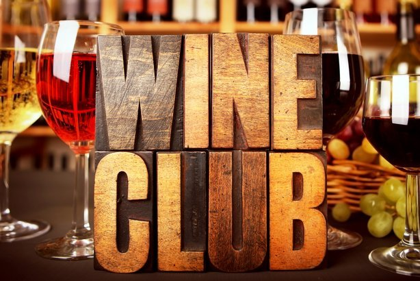 'Wine Club' in letterpress letters in front of wine racks with wine and grapes
