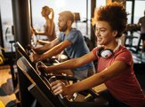 happy black athlete practicing on exercise bike in a health club