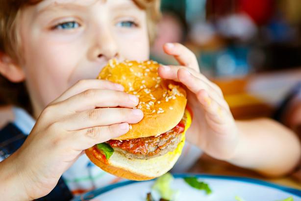 Little boy eating a burger