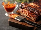 barbecued ribs and barbecue sauce on wood cutting board