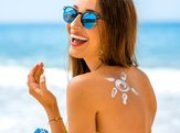 woman with sun shape on the shoulder holding sun cream bottle on the beach