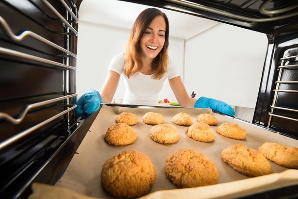 happy woman baking fresh cookies in oven at kitchen