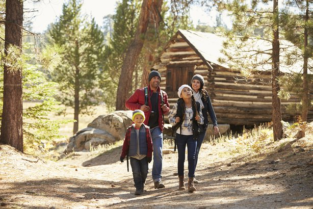 family walking away from a log cabin in a forest