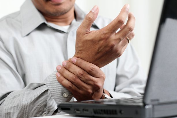 man at laptop holding pain in wrist