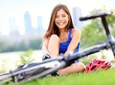 woman smiling laying in park with bike on the ground