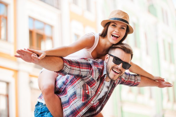 happy young man piggybacking his girlfriend while keeping arms outstretched