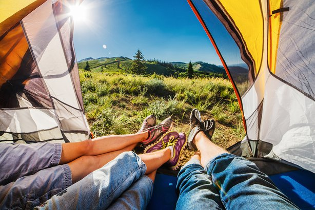 feet hanging out of tent and showing scenery