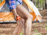 woman applying bug spray outdoors near camping site